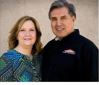 Male and female owners smiling in front of a cream background.