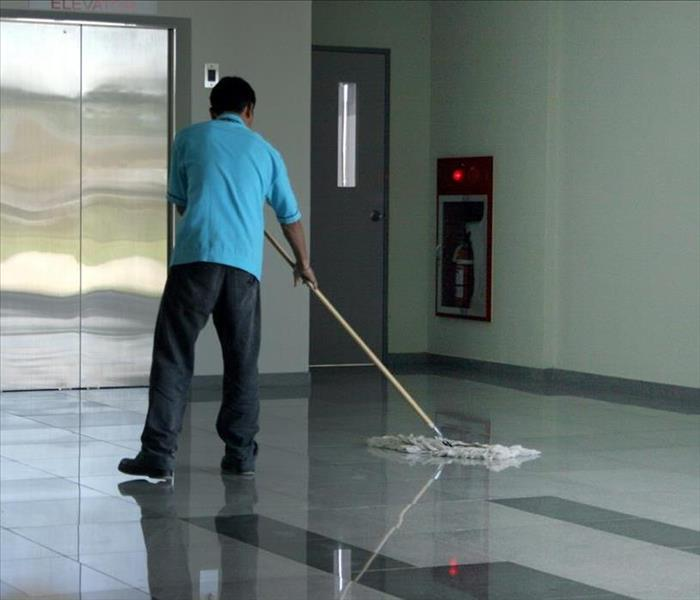 Man mopping floors in a lobby in from of an elevator.