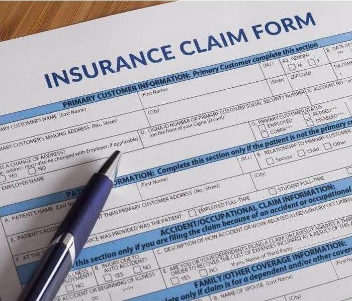 Insurance claim form and a pen laying on the table.